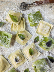 fresh cut square raviolis with herbs on floured board