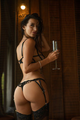 Back view body of fashion model indoors. Beauty brunette woman with attractive body in black lingerie standing in the bedroom with glass of champagne. Female ass in underwear