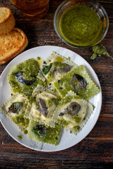 plate of square raviolis with herbs, olive oil, and pesto sauce