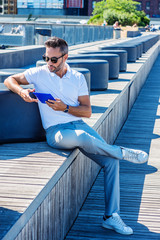 Modern Reading. Young European Man with beard, little gray hair, wearing white Polo shirt, gray pants, white sneakers, sunglasses, sitting on stairs at street park in New York, reading tablet computer