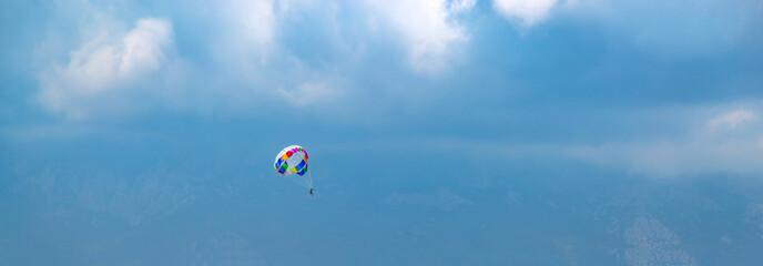 Человек с парашютом в голубом небе в облаках, над горами