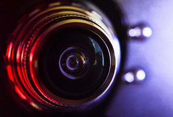 The camera lens and light reddish-purple color . Close up. Horizontal photography