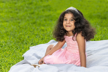 A young girl surrounded by green grass is sitting on a white blanket
