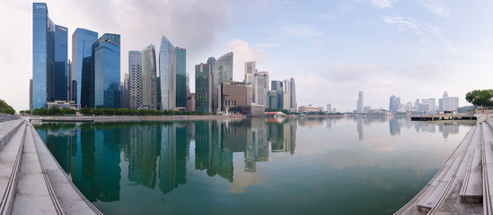 Singapore's Central Business District skyline at sunrise, with high rise buildings and waterfront, from Marina Bay terrace deck.