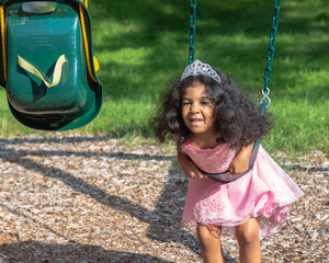 A toddler is trying to sit on the swing at the playground