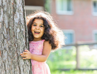 A young girl is hiding behind a tree