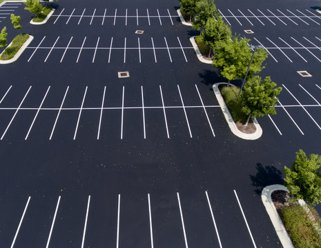 parking lot,asphalt,island,trees,stalls,parking stalls,paint,green