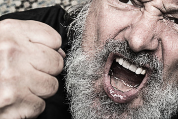 aggressive crying man with a clenched fist, open mouth snd  grey full beard