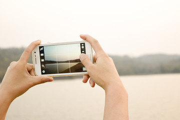 Young woman with smartphone taking photo of Landscape view. Telecommunication and technology device