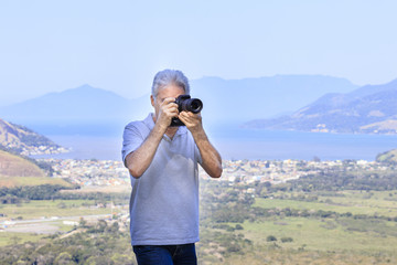 Senior man photographing landscape with modern camera