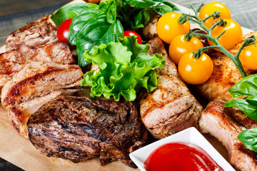 Assorted delicious grilled meat and vegetables with fresh salad and bbq sauce on cutting board on wooden background close up