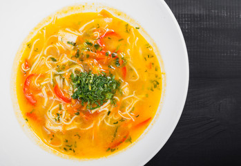 Vegetable soup, broth with noodles, herbs, parsley and vegetables in bowl on wooden black background, healthy food. Top view