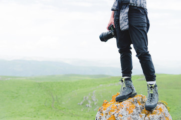 Photographer holding a camera outdoors. Girl on nature