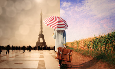 Young girl in coat with suitcase and umbrella walking along a rural road on one side and parisian square on other. Wall mural