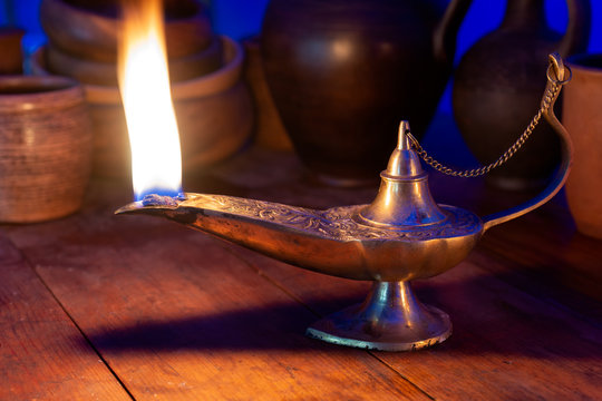 Ancient oil lamp burns on a wooden table