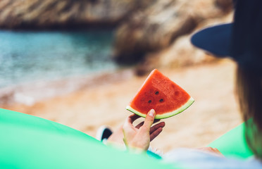 girl hipster relax on beach coast and holds in hand a slice of red fresh fruit watermelon on blue sea background, woman on seaside nature eating sweet healthy food, vacation in summer concept