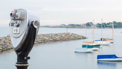 vintage tower viewer overlooking anchored sailboats and a rock breakwater at a small harbor in Massachusetts