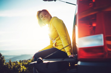 Wall Mural - tourist traveler traveling in car on top mountain, young girl smiles happily against background sunset in mountains hills, happy girl enjoying nature panoramic landscape in trip, relax holiday concept