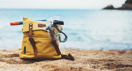 Hipster hiker tourist backpack and swimming mask on background sea ocean horizon on sand beach, blurred panoramic seascape blank, traveler relax holiday concept, sunlight view in trip vacation