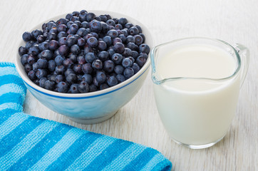 Raw blueberry in glass bowl, jug of milk, striped napkin