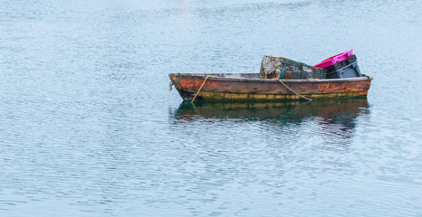 solitary rusted rowboat filled with a lobster trap and plastic buckets floating in a Massachusetts harbor with copy space