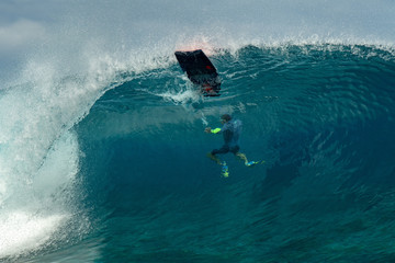 Surfer inside wave tube in Polynesia