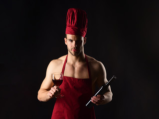 Restaurant. Wine making. Male sommelier tasting red wine. Chef or sommelier, man in cook hat, apron. Sexy male chef in burgundy cook hat and apron with red wine. Italian style and sommelier concept.