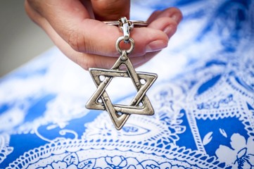 Young woman's hand holding a Star of David - Magen David key chain. The State of Israel, Holocaust remembrance, Judaism, Zionism concept image. Wall mural