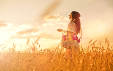 Woman in wheat field at sunset