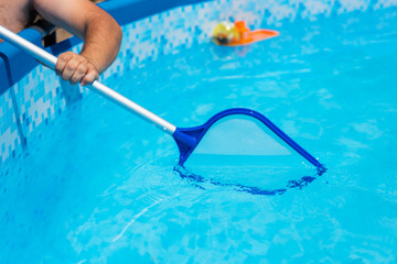 Backyard garden swimming pool cleaning close up
