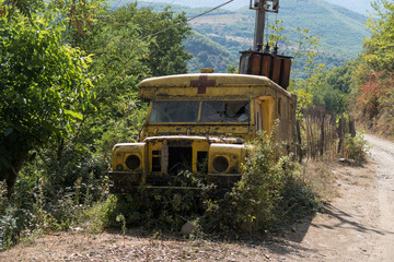 Old ambulance car decaying and corroding in the wilderness of Albania
