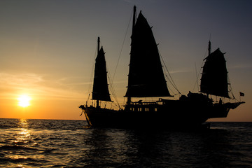 Old junk style sailboat sailing into the sunset of the Andaman Sea in Thailand