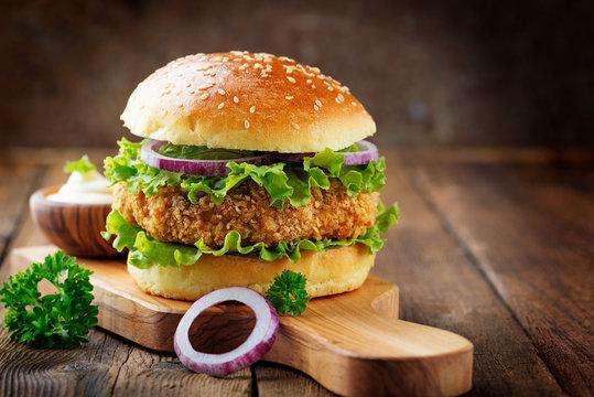 Fresh tasty chicken burger on wood table.