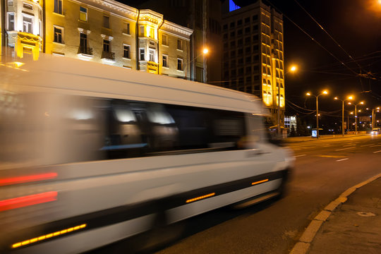 Motion blurred white minibus on the street in the evening.