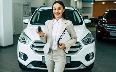 Beautiful smiling saleswoman in full suit in dealership on cars background with car keys and documents in hands