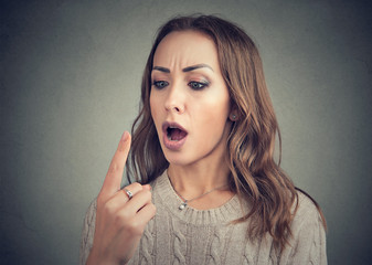 Shocked woman looking at her finger has double vision