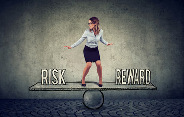 Skillful young business woman balancing between reward and risk