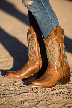 Female in brown cowboy boots on gravel road