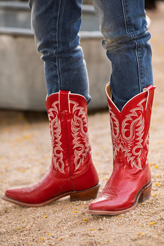 Female in red cowboy boots on gravel road