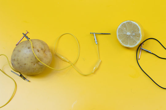 Potato battery STEM activity with potatoes, lemons, alligator clips, zinc and copper nails. Natural battery to turn on a led. scientific experiment for children on electricity on yellow background