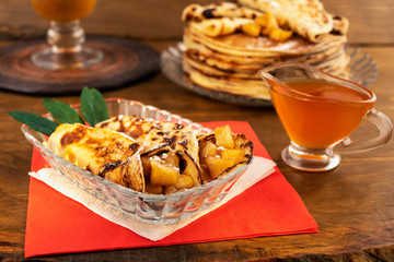 Fried pancakes with apple  filling, honey in a glass gravy boat, a stack of pancakes in the background, all on a wooden background.