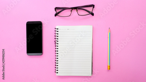 Wall mural Workplace with blank notebook and smartphone on pink background.(Top-view )