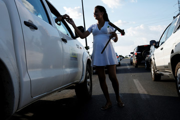 Anyi Gomez, 19, a pregnant Venezuelan woman from Monagas state, receives money after washing car windows at a traffic light in Boa Vista