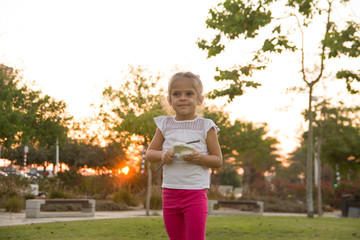 Portrait Adorable Little Girl Smiles outdoor at sunset. cute girl make snow from styrofoam.