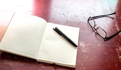 Wall Mural - Notebook with pen and glasses on wood table background