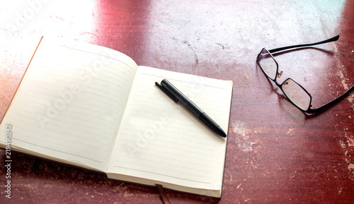 Wall mural Notebook with pen and glasses on wood table background