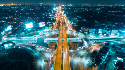 Aerial view highway road intersection at night for transportation, distribution or traffic background.