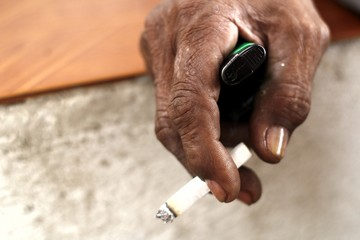 Hand holding a cigarette and a lighter