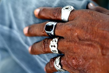 Hand of an old man with rings on each finger