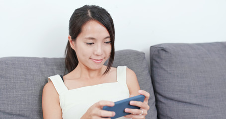 Woman play game on smart phone at home
